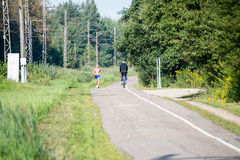 Man jogging and man cycling on the road Stock Photography