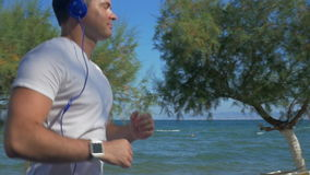 Man jogging with music at the seaside stock video footage
