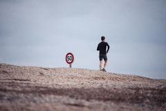 Man jogging next to road sign Stock Photos