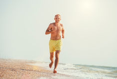 Man jogging on the sea surf line at morning time Royalty Free Stock Photography