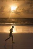 Man jogging on tropical beach. Young male runner jogging on tropical beach at sunrise, Diani beach kenya Royalty Free Stock Images