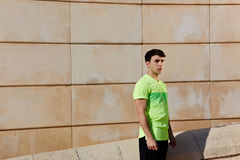A man jogging in the warm sunny day. Portrait of young athletic man standing against brick wall background at sunny day, ready to workout and exercise outdoors royalty free stock photography