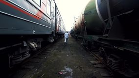 The man jogs against the background of two trains. Male athlete runs among the trains, explosive power stock footage