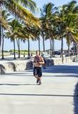 Man jogs along along the promenade at ocean drive in South Beach Stock Images