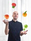 Man juggle fruits Stock Photos