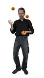 Man juggles with oranges Stock Image