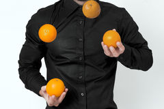 Man juggling. Man in black shirt juggling with oranges Royalty Free Stock Images