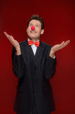 Man juggling. Cheerful man with a clown nose juggling while stan. Ding  on red Stock Photography