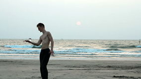 Man juggling with glass ball on the beach. Goa, India – February 10, 2016: Unidentified man juggling with glass ball on the beach stock video footage