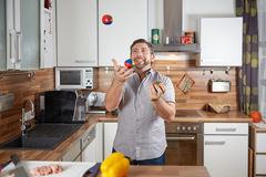 Man juggling in the kitchen with tomatoes Stock Images