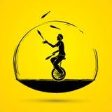 A man juggling pins while cycling Stock Image