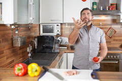 Man juggling with tomatoes in his kitchen laughing Royalty Free Stock Photo