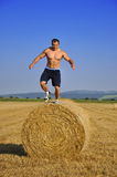 Man jump down from bales of straw Stock Photo
