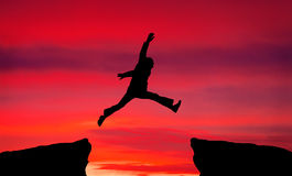 Man jump through the gap on sunset fiery background. Stock Photography