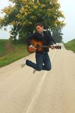 Man jump with guitar. Young musician jump with guitar over asphalt road royalty free stock images