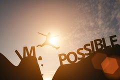 Man jump between impossible wording and possible wording on mountain. Mindset for career growth business