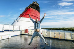The man in the jump poses on the upper deck of the ferry Stock Image