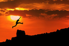 Man jump through the rock. Silhouette of man jump through the rock. Shot outdoor at dawn Royalty Free Stock Photos