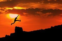 Man jump through the rock. Silhouette of man jump through the rock. Shot outdoor at dawn Royalty Free Stock Photos