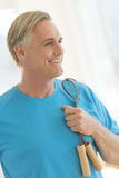 Man With Jump Rope Looking Away In Gym Stock Image