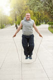 Man with jump rope in park. Royalty Free Stock Photo