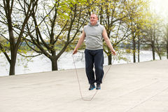 Man with jump rope in park. Stock Photo