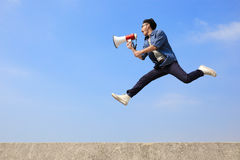 Man jump and shout megaphone. Man jump and shout by megaphone with blue sky background, asian Stock Photos