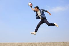 Man jump and shout megaphone. Man jump and shout by megaphone with blue sky background, asian Royalty Free Stock Photo