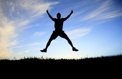 Man jump on the sunset day time Stock Images