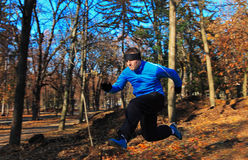 Man jumping. Over a hole in a beautiful forest in autumn Royalty Free Stock Image