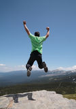 Man jumping. With hands raised mountains landscape with blue sky and clouds as background Royalty Free Stock Image