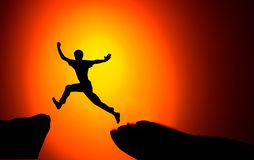 Man jumping across the gap from one rock to cling to the other. Man jumping over rocks with gap on sunset fiery background. royalty free stock photography