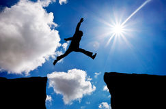 Man jumping across the gap from one rock to cling to the other. Royalty Free Stock Photography