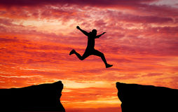 Man jumping across the gap from one rock to cling to the other. Royalty Free Stock Image