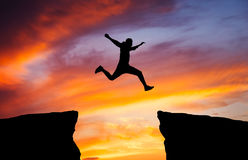 Man jumping across the gap from one rock to cling to the other. Stock Image