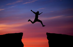 Man jumping across the gap from one rock to cling to the other. Stock Photography