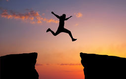 Man jumping across the gap from one rock to cling to the other. Royalty Free Stock Photos