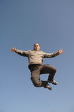 Man jumping against blue sky. Middle age man jumping against blue sky of happiness Royalty Free Stock Photography