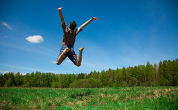 Man jumping against blue sky Stock Images