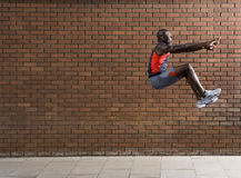 Man Jumping Against Brick Wall Royalty Free Stock Photos