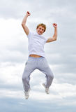 Man jumping in air against sky. Royalty Free Stock Image
