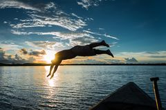 A man jumping into the Amazonas river. For sunset, Peru stock image