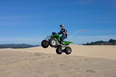 Man jumping ATV in sand dunes Royalty Free Stock Photo