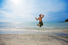 Man jumping by the beach happi. Happy man jumping excitedly by the beach Royalty Free Stock Image