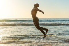 Man jumping on beach at sunset Royalty Free Stock Photography