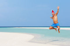 Man Jumping On Beach Wearing Santa Hat Royalty Free Stock Photos