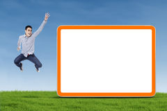 Man jumping with blank board Stock Photo