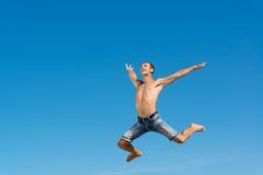 Man jumping on the blue sky background. A good time Royalty Free Stock Image