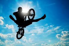 Man jumping on bmx bike performing a trick. Sunny sky Stock Photos