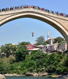 Man jumping from the bridge in old town of Mostar Stock Images